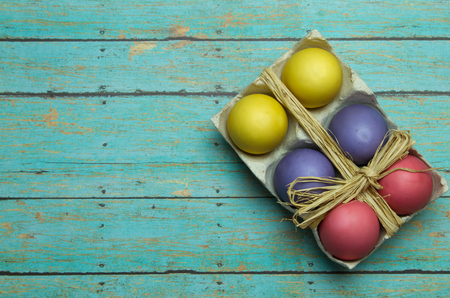 multi color: Multi Color dyed easter eggs on a wooden plank background wrapped in a twine bow