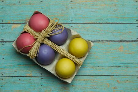 multi color: Multi Color dyed easter eggs on a wooden plank background with room for copyspace