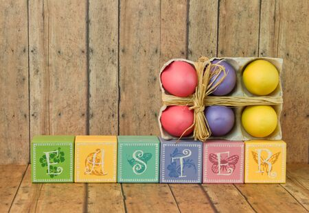 multi color: Multi color Easter blocks with twine bow easter eggs on a wood plank background