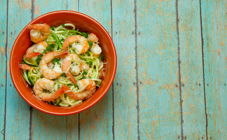 spiralized: Bowl of spiralized zucchini topped with jumbo shrimp on wood plank board