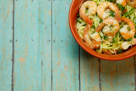spiralized: Fresh jumbo shrimp bedded on spiralized zucchini on a wood plank board Stock Photo