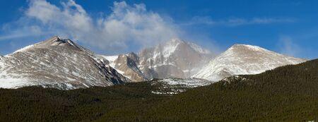 longs peak: Clouds roll over a snow capped Longs Peak in Colorado