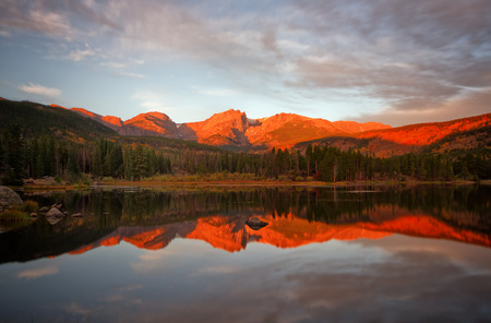 rocky mountain national park: Beautiful alpine glow on Hallet Peak and the Continental Divide. The mountains reflect in Sprague Lake. This beautiful lake is located in Rocky Mountain National Park outside of Estes park Colorado Stock Photo