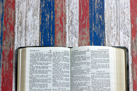 An open Bible against a July 4th red, white and blue background Stock Photo