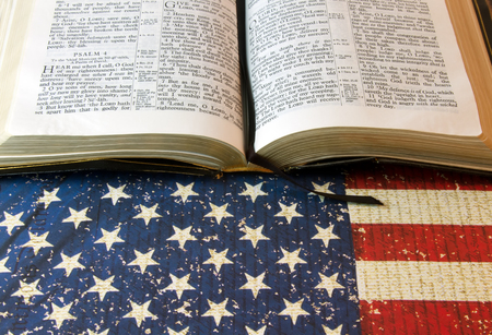 The Holy Bible laying on a background of the American Flags with her stars and stripes Stock Photo