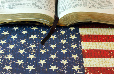 The bookmark hangs out of an opened bible with a background copy space of red, white, and blue