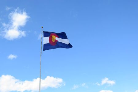 colorado flag: The Colorado flag waves proudly against a blue sky with a few clouds in the distance