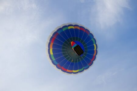 float cloud: A colorful multi color hot air balloon floats among the clouds and the blue sky