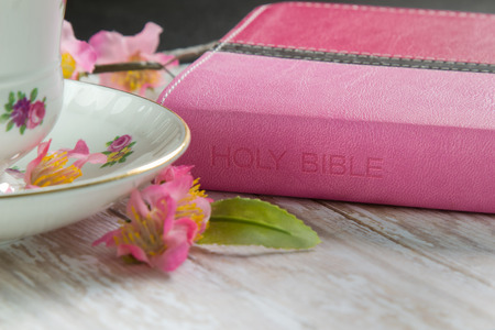 A Pink Holy Bible on a wood plank board with a cup of coffee or tea surrounded by pink spring flowers