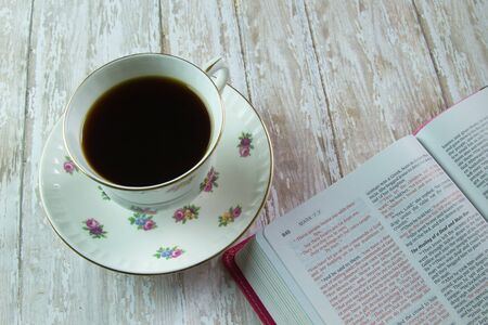 The Holy Bible opened to the book of Mark with a flowered tea cup filled with coffee or tea