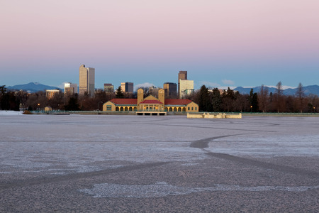 denver skyline with mountains: Early morning sunrise on Denver City Park in the winter with a frozen lake