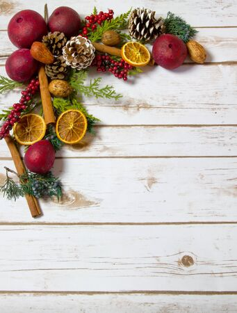 potpourri: Christmas Potpourri background with oranges, dried fruit, cinnamon sticks, nuts with room for Copy Space on wood plank board Stock Photo