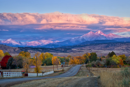 Longs Peak lights up at sunrise as a rural country road leads into the fall trees