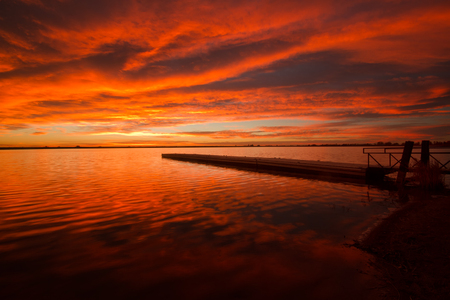 Bursting red sunrise on the boat dock on a Colorado lake