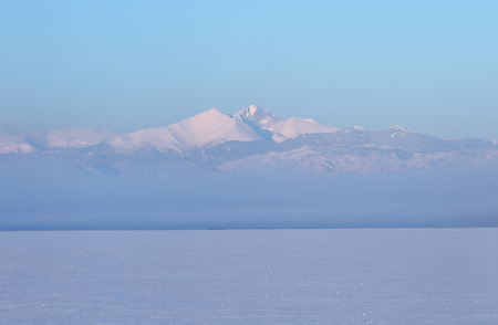 Fog settles on the snowy landscape with Longs peak covered in snow on a winters morning Stock Photo