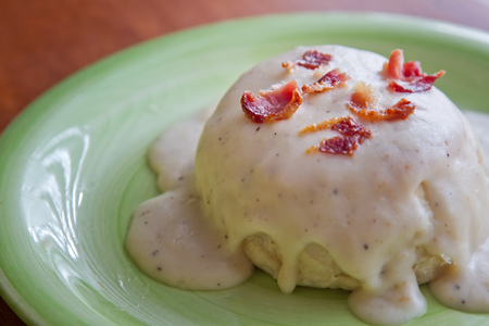 biscuits: Biscuits and Gravy topped with bacon on a green plate Stock Photo