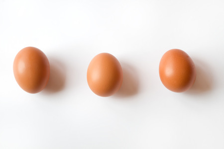 Three Fresh Organic Brown Eggs isolated on a White Background all lined up in a row Stock Photo