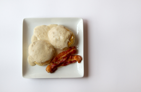 biscuits: Biscuits and Gravy with two slices of Bacon on a white plate isolated on a white background Stock Photo