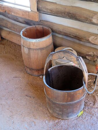 antique water or drinking barrels sitting next to a log cabin Banco de Imagens