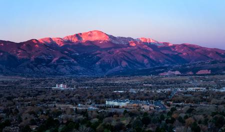 Pikes Peak의 정상 회담은 아침 일출에 빛난다. 거리와 사업 사무실은 산 아래에있다. 거리의 신들의 정원을 볼 수 있습니다. 스톡 콘텐츠