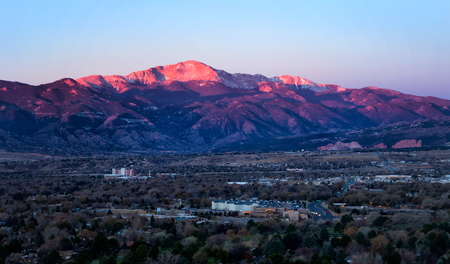 The summit of Pikes Peak glows in the morning sunrise as the streets and business office are below the mountain. Garden of the Gods can be seen in the distance