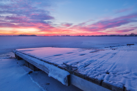 very cold: Pink Clouds form over a Colorado Lake and the fishing dock on a very cold winters morning Stock Photo