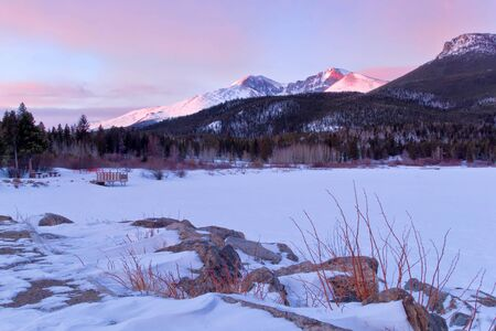 longs peak: The summit of Longs Peak glows with a snow covered Lily Lake in the foreground Stock Photo