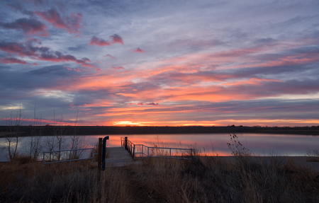 The sky bursts with color at sunrise on Lon Hagler Reservoir in Loveland, Colorado