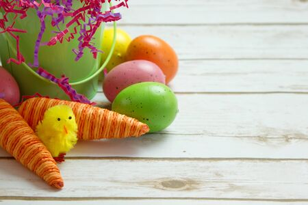 Orange striped faked carrots and colorful Easter Eggs with a spring chick on a rustic whitewashed wood background with room for text Stock Photo