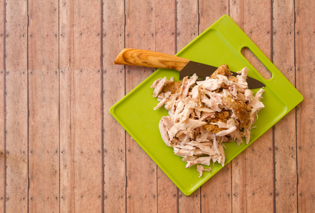 Shredded rotisserie chicken on a green plastic cutting board and carving knife against wood plank background with room for copy space