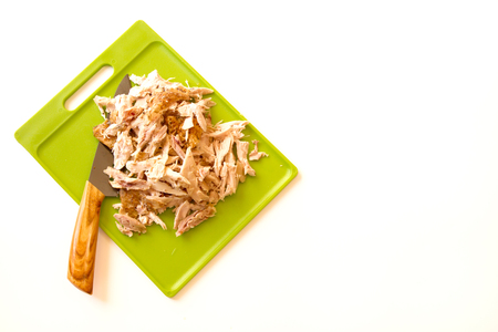 Shredded rotisserie chicken on a green cutting board and carving knife isolated on a white background with room for text or copy space Stock Photo