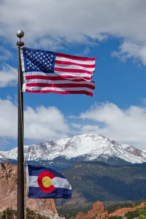 American and Colorado Flag waving in the wind with Pikes Peak and Garden of the Gods in the background Stock Photo