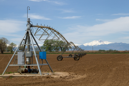 A Pivot Irrigation System in a farming field with Longs Peak Mountain in the background on a sunny day Stock Photo
