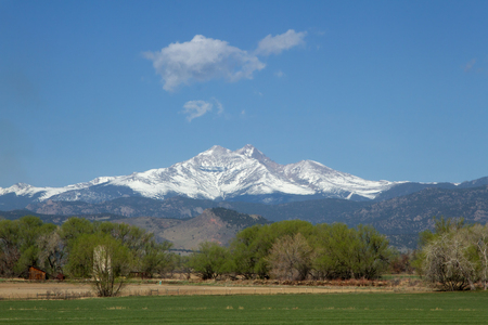 Beautiful view of the snow capped Longs Peak and Mt Meeker with spring green field and trees in the foreground