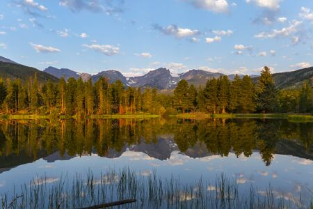 Beautiful warm light hits the evergreen trees along Sprague Lake in Rocky Mountain National Park