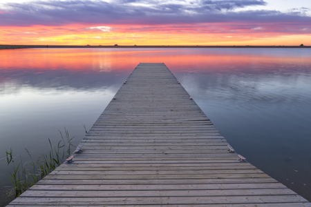 sunrise or sunset over a fishing dock or fishing pier with colorful clouds reflecting in the lake located in Larimer County, Colorado