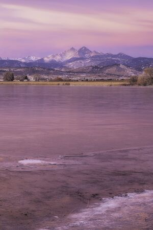 The lakes are starting to freeze over for the winter as the sunrise over Longs Peak Mountain glows in Pink in Northern Colorado Stock fotó