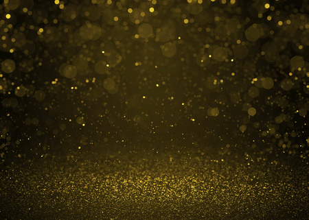 Highlighted bokeh gold sparkle glitter background. Defocused glitter stars background