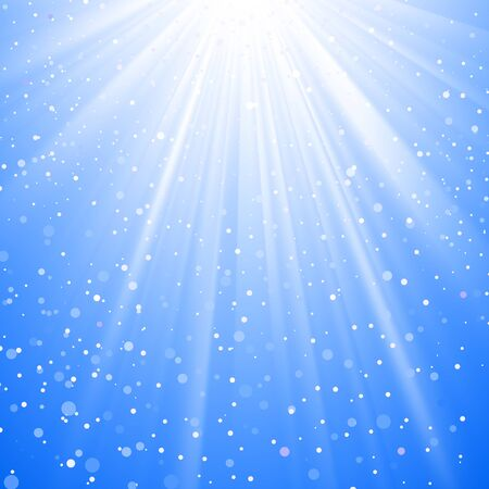 spot lit: Shining sunbeams from above with snow flakes on blue sky background