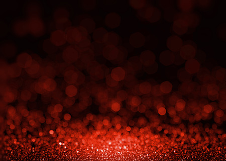 Red beautiful glitter sparkles. Textured fashion glamour sequins background. Christmas glittering wallpaper. Ruby gem shining splatter.