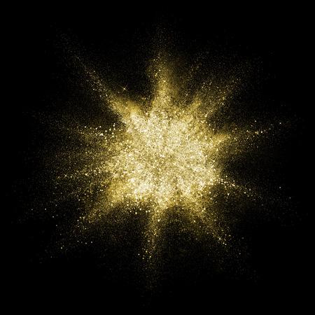 Gold glitter powder explosion. Golden color dust splash. Particles burst with golden texture for fashion background, luxury wallpaper. Magic mist glowing. Powdered vivid gold on black background. 版權商用圖片