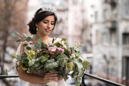 bride with a bouquet of flowers on the balcony Stock Photo