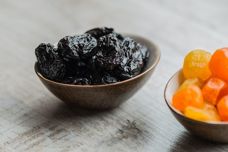 two plates with dried fruits on wooden background: dried mandarins and prunes.