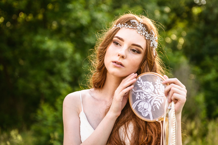 young redheaded girl smiling and hold dreamcatcher