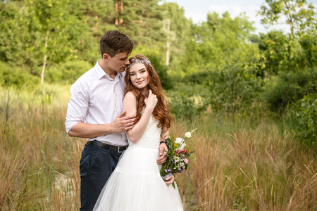 path to romance: young couple in the ears of wheat in forest