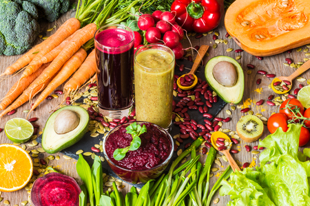 Healthy vegan food. Fresh vegetables on wooden background. Detox diet. Different colorful fresh juices Imagens