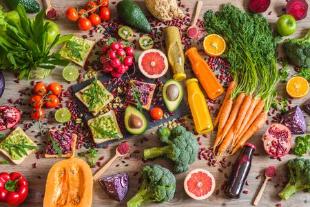 Comida vegana saludable Verduras frescas sobre fondo de madera. Dieta de desintoxicación. Diferentes coloridos jugos frescos. Foto de archivo - 75140884