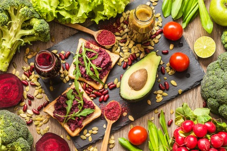 Healthy vegan food. Sandwiches and fresh vegetables on wooden background. Detox diet. Different colorful fresh juices Stock Photo