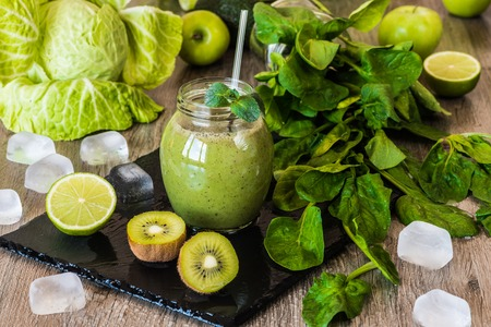 spinage: Detox diet. Green smoothie with fruits and vegetables on wooden dark background