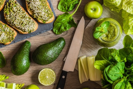spinage: Detox diet. Green smoothie and sanwiches with avocado. Different vegetables on wooden background
